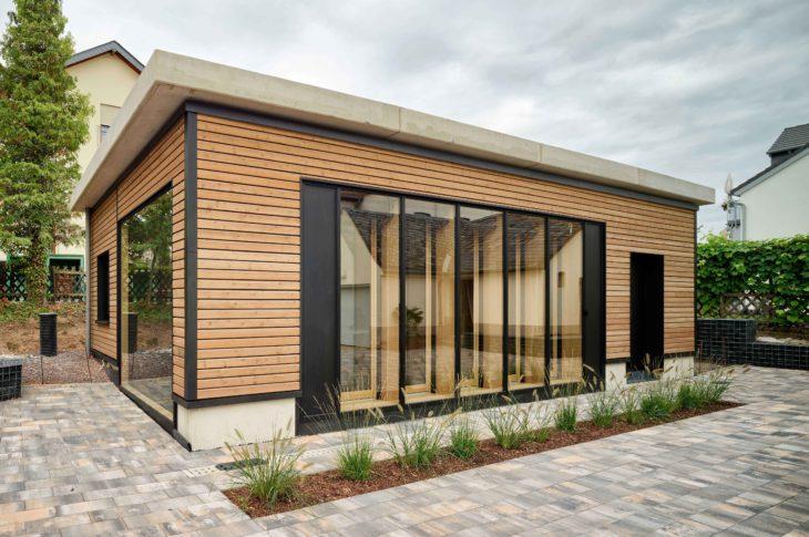 Auf dem Bild ist das energieautarke InnoLiving Gebäude in Kues zu sehen. Die Außenfassade, welche aus Holz-Betonverbundwänden besteht, wird gezeigt.
